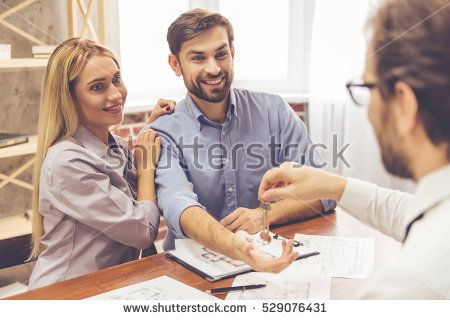 Beautiful couple is taking keys from the realtor and smiling