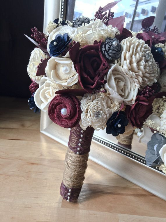 This beautiful handmade bouquet was intricately designed by me using natural colored sola flowers, hand dyed burgundy, navy, and grey sola flowers, preserved babies breath and preserved dyed burgundy seeded eucalyptus. The handle is wrapped in twine and finished with burgundy lace and pearl pins. The bouquet pictured is an extra large, the last photo shows the extra large bridal bouquet with a medium bridesmaid bouquet.  Colors can be customized/substituted. Please message me or add your...