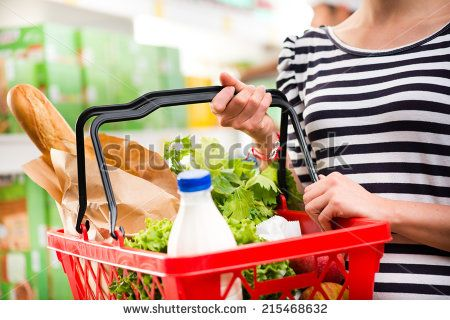 Woman shopping at store with shopping basket. - stock photo