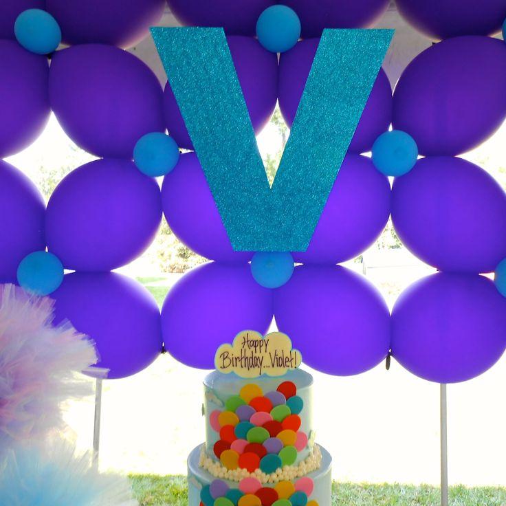 Balloon birthday cake and balloon backdrop center the dessert