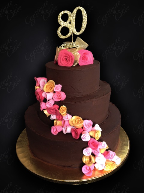To Nana With Love: This big and beautiful 80th birthday cake has three tiers of chocolate mud cake, lashings of chocolate ganache and a spray of bright flowers to finish.