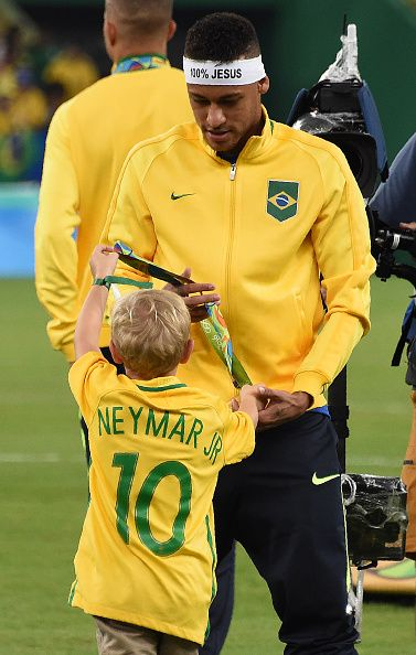 Brazil's forward Neymar walks with a child after the Rio 2016 Olympic Games…