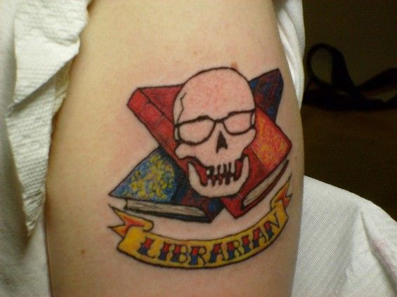 """Prefer your ink a little more hardcore than most of these librarian tattoos? Then, you'll probably approve of Jason Puckett's tattoo by Ron Hendon of Midnight Iguana Tattooing that features a bespectacled skull with """"crossbooks"""" and a """"librarian"""" banner."""