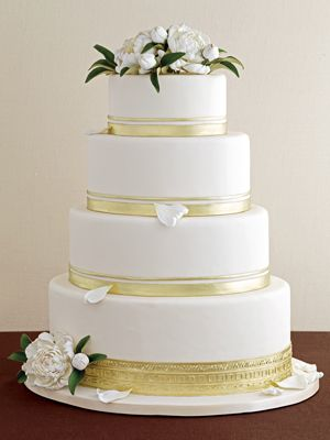 A Gilded Gold Oval Wedding Cake  It's the oval-shaped tiers that give this gold-banded cake with lifelike sugar flowers a fresh look