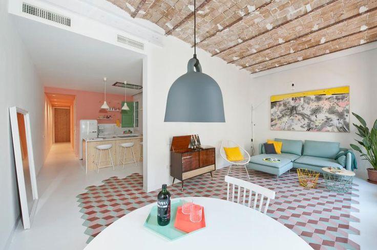 Appartamento vacanze a Barcellona. L'open space che raccoglie living e sala da pranzo da un lato e ingresso con cucina a vista dall'altro. A fare da trait d'union il pavimento in cementine esagonali colorate e cemento bianco. Sul tavolo vassoio Kaleido di Hay.