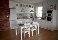Białe meble z miętowymi lampami w aranżacji jadalni