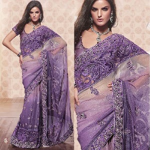 Captivating sequins work saree -- Stir your fashion sense dressed in this charming silverish brinjal shade of shimmer georgette saree. The charming designs adorning the body and pallu is embellished with sequins and embroidery. It is garnished by a lovely border and paired with a matching blouse. $192