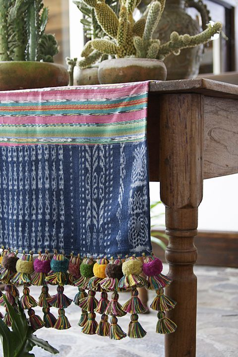 gorgeous textile with pom tassels on wood.