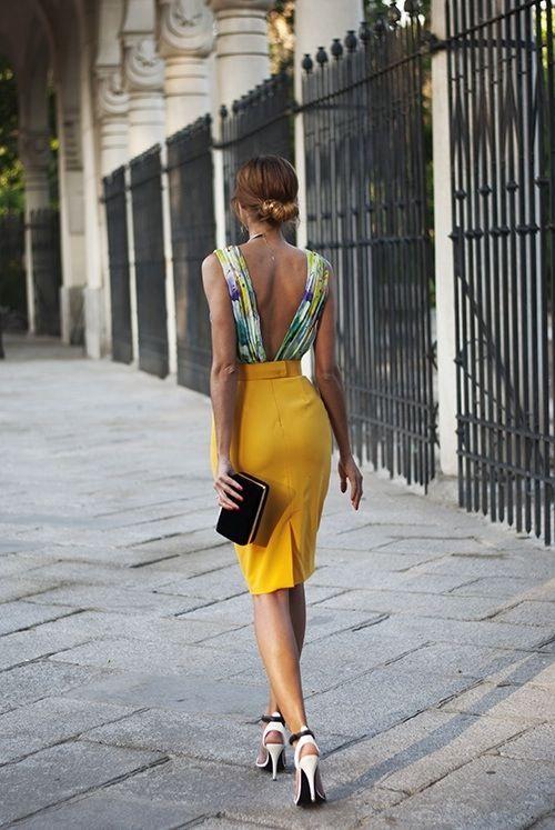 Vestido para invitada de boda. Falda lapiz color mostaza y la blusa con estampado de colores verdes amarillos y morado y la espalda descubierta. Outfit perfecto con clutch negro. Peinado recojido con moño bajo y con look despeinado
