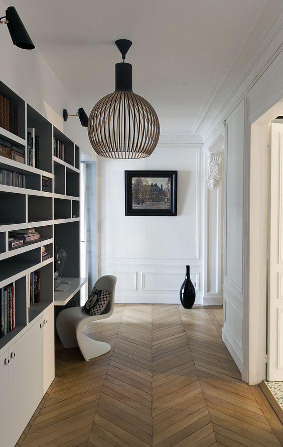 Un coin bureau dans la continuité d'une bibliothèque qui s'aménage dans un couloir