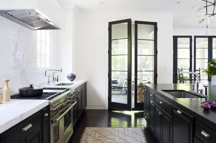 Dramatic tall black French doors in an urban chic kitchen with black and white. Design by Ella Scott Design. Come see the dramatic Before & After: Fussy Traditional to Urban Chic! #blackandwhite #modernkitchen #blackandwhite #urbanchic #blackcabinets #benjaminmooreblackpanther #benjaminmooremoonlightwhite