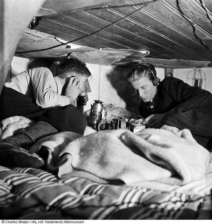 Onderduikers Jan en Joop Kuyt luisteren naar radio, Oranje Nassaulaan 15, Amsterdam (1945) Maker: fotograaf: Charles Breijer Verv.jaar: 1 maart 1945/31 maart 1945 Verv.plaats: Amsterdam