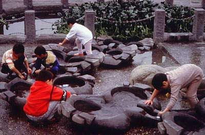"""Betsy Damon, """"The Living Water Garden"""", Chengdu, Sichuan Province, China, 1999. Young park visitors play on the flow forms, sculptures that aerate the water before it enters the constructed wetlands."""