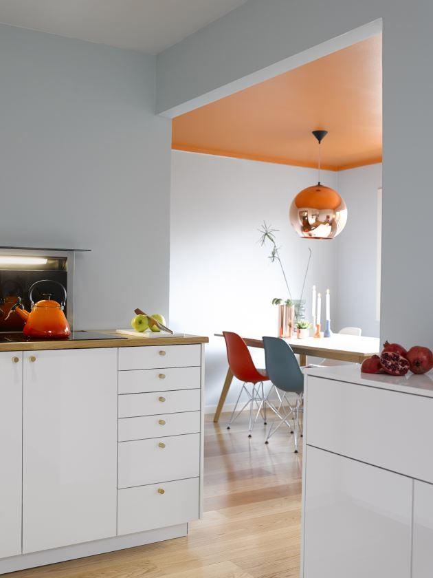 Svale, matte vegger og hvit, blank kjøkkeninnredning skaper behagelige rammer mot vitamininnsprøytningen takfargen utgjør; S 1070-Y70R.