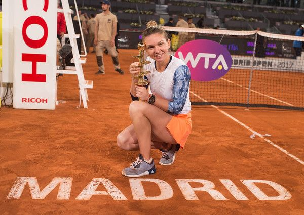 Simona Halep of Romania celebrates with the trophy after beating Kristina Mladenovic of France in their final match during day eight of the Mutua Madrid Open tennis at La Caja Magica on May 13, 2017 in Madrid, Spain.