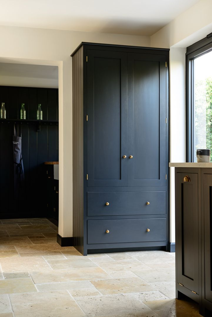 A beautiful deVOL Shaker pantry cupboard painted in our 'Pantry Blue' colour with 'Bella Brass' knobs, perfect with this Country Mixed Tumbled Travertine floor from our sister company @floorsofstone