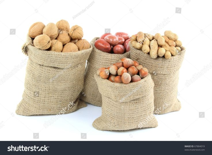 Still life picture of different Kinds (Sorts, Types) (Walnuts, Pecan, Peanuts, Hazelnuts) Nuts with shells in burlap bags over white background.