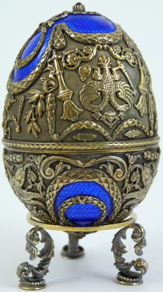 FABERGE RUSSIAN SILVER  ENAMEL EGG w STAND - Incredible Russian silver  cobalt enamel egg by Faberge. Has intricate raised design depicting the Russian double headed eagle, torches, wreaths and griffins. Mounted with Cabochon garnets to top and bottom. Gold wash interior. Has Ivan Lebedkin, Moscow town marks with 88 silver purity mark. Has cyrillic Faberge mark