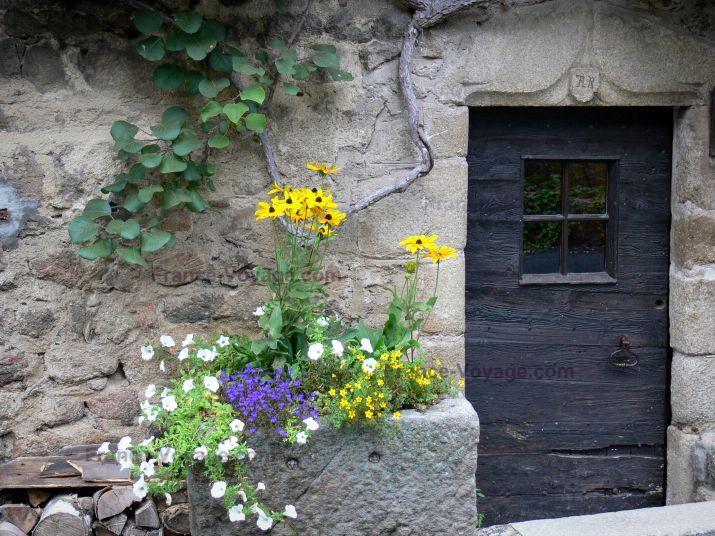 Moulin Richard de Bas: Site du moulin à papier : porte d'entrée d'un bâtiment et fleurs ; sur la commune d'Ambert, dans le Parc Naturel Régional Livradois-Forez - France-Voyage.com