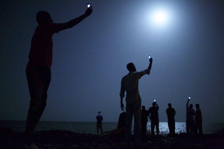 """Premios World Press 2013. La fotografía titulada """"Señal"""", realizada por el estadounidense John Stanmeyer, ganó el World Press Photo, según informó la organización del galardón con sede en Amsterdam (Holanda). Un grupo de inmigrantes africanos busca cobertura para sus teléfonos móviles en la orilla de Yibuti."""