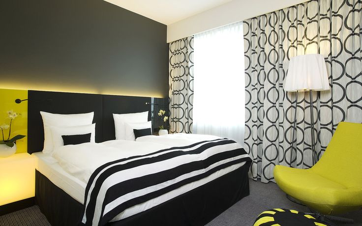 Yellow, black, grey and white colours rule at the Vienna House Andel's Berlin. #Hotelroom #bedroom #interiordesign #hotel