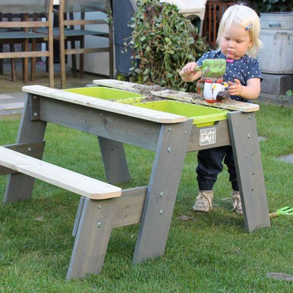 Hiekkalaatikkopöydän ääressä lapsella on puuhaa