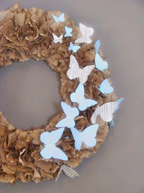 basiskrans zijn rondjes geponsd uit bruin papieren boterhamzakjes. De vlinders zijn gestanst uit boekpagina's en lichtblauw cardstock. Alles met lijmpistool op isomo krans gekleefd.