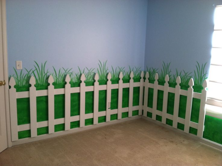 Picket fence along painted grass