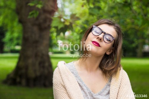 Beautiful young woman smiling at the sun in the park