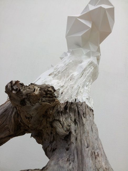 White polyhedric plaster sculpture on a tree trunk