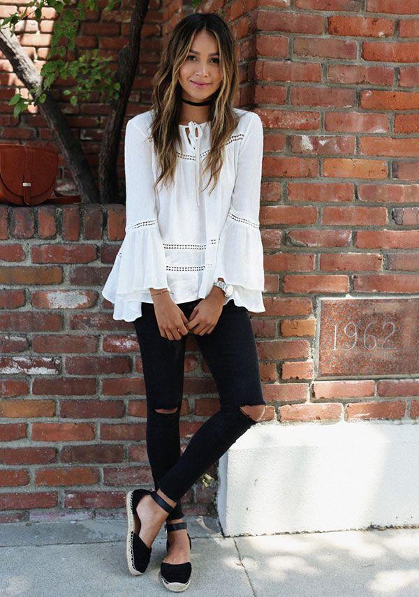 Street style look com calça preta rasgo no joelho, espadrille preta com amarrações e bata branca com manga flare.