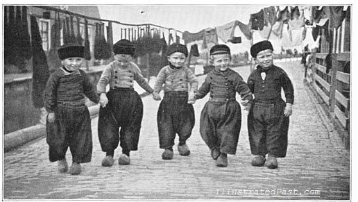 Dutch boys wearing clogs march down a quiet cobblestone street. Their clogs must have made quite the racket.