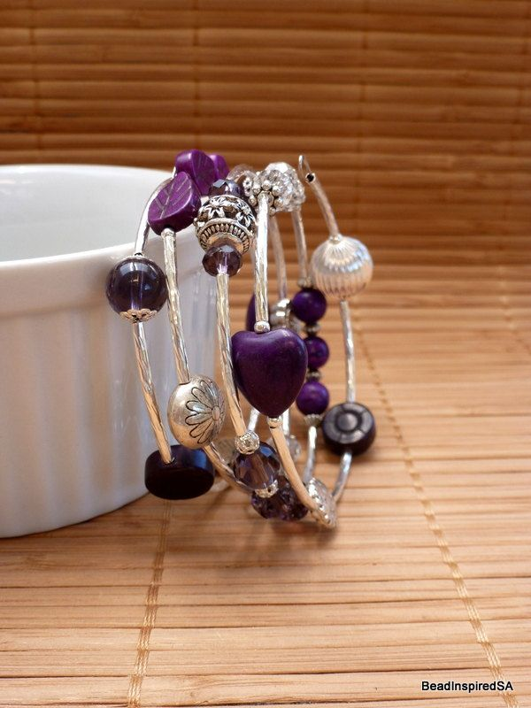 This adult Purple and Silver memory wire bracelet wraps around 4 times and has a random mix of glass, magnesite and silver plated beads in gorgeous shades of purple, clear and silver. Bead types range from faceted, round, rondelle, oval, flower, heart, leaf and butterfly. Bead sizes range from 4mm to 14mm. The beads are separated with silver plated tube beads, silver plated daisy spacer beads and small round silver plated beads. Silver plated bead caps are also used. Memory wire is my all…