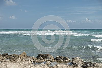 A picturesque view of the wild tropical beach with waves  and rocks in Maya Riviera, Mexico.