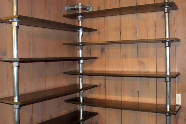 Finding a bookshelf that will fit into the corner of a room is a difficult task. When faced with that scenario, Rachel, from Upstate New York, turned to Kee Lite pipe fittings.  She transformed a fairly ho-hum rustic space into a more modern office area through the addition of some paint, flooring and industrial-styled furniture such as this corner pipe shelf.