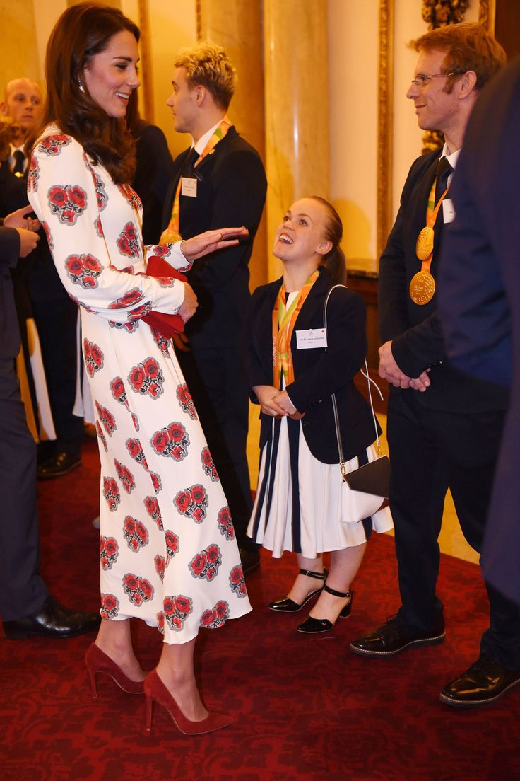 October 18, 2016 - The Duchess wears a rose-patterned Alexander McQueen dress with red suede pumps and a red clutch while meeting Olympic and Paralympic athletes at Buckingham Palace.