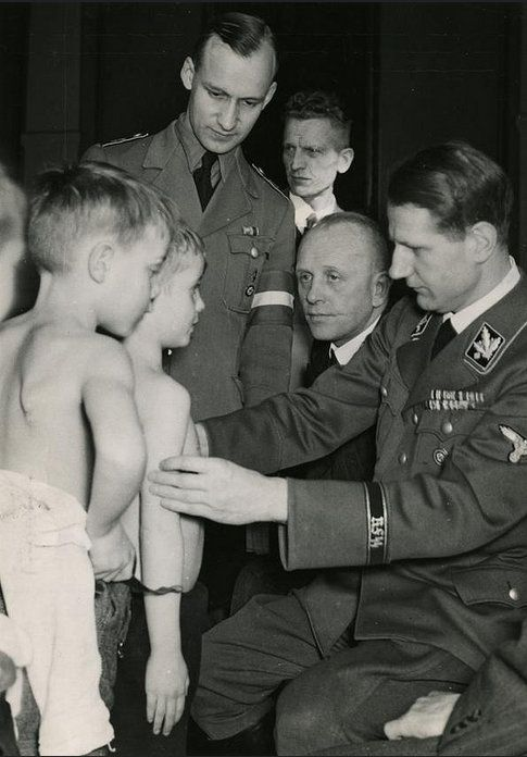 "Dr. Leonardo Conti, SS-Gruppenführer and Reich Health Leader (Reichsgesundheitsführer) examines a group of children. He was responsible for the ""mercy killing"" of hundreds of Germans of ""unsound mind."" While in prison and awaiting trial for war crimes associated with the Nazi Euthanasia program (T4), Conti hanged himself in his cell on Oct 6, 1945."