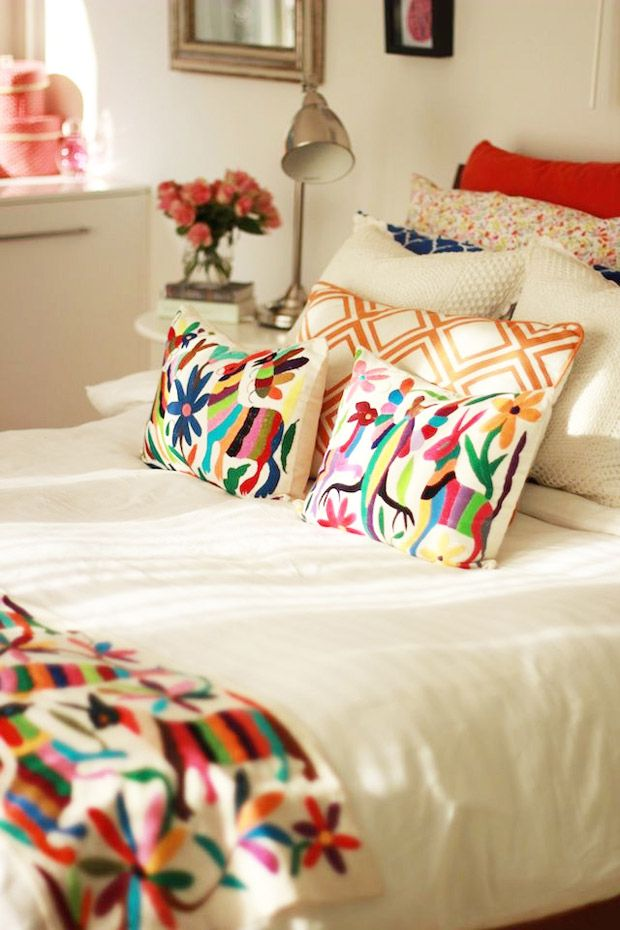 Lushly colored Otomi textile pillows and coverlets against a sea of white, so crisp and fresh
