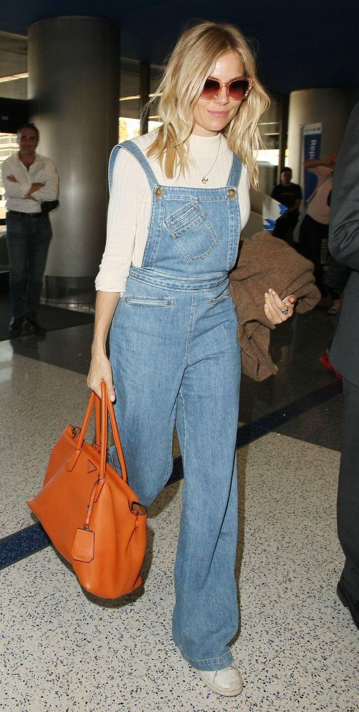 Sienna Miller in a mock turtleneck, overalls, and orange Prada tote.