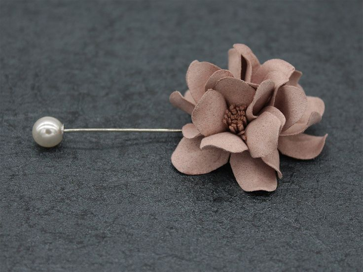Beautiful Brown Lapel Flower: The stigmas are made of vertical fabric sticks. The brown flower has a silver pin attached to the end of the other side of the pin having an off-white bead. bowselectie.com