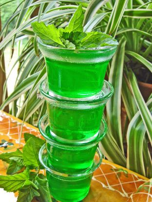 Cuban Jello Shots! Minty Lime! Can use Marti Mojito Rum if available where you live.In these pictures I made it in my vita mix so I didn`t have to strain the mint.That is why you see a head on the shots in the picture.