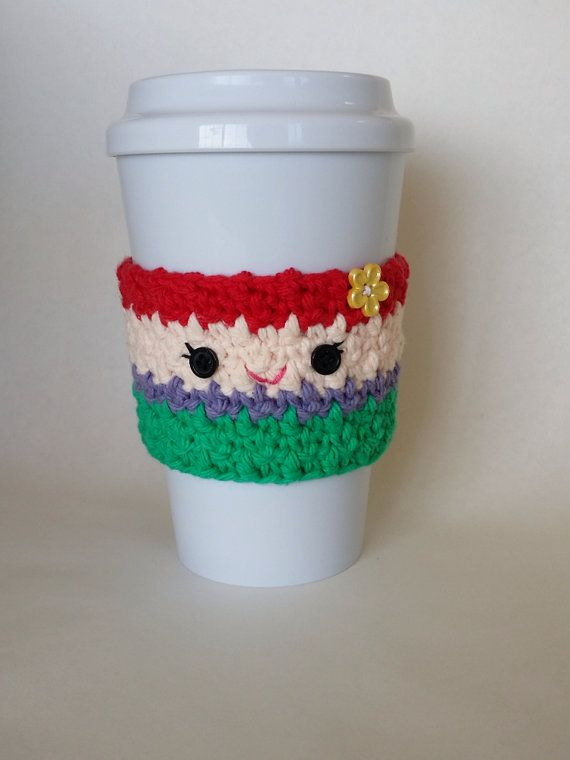 A cute and fun handmade crochet Little Mermaid Ariel coffee cup cozy!    Perfect for Disney and Ariel fans, this cozy will keep your hands safe from hot coffee cups and you can feel good about being environmentally friendly too because you can reuse it!    Will fit most standard coffee house cups.    Hand made with cotton yarn in a smoke free home.  Each cozy is made to order and the yellow button style may vary from one pictured.    Not recommended for small children because buttons can be…