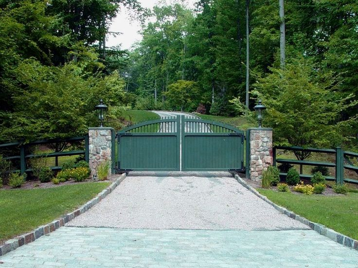 A transitional-style driveway entry gate is painted forest green to match with the existing post-and-rail fence. Driveway gate designed and installed by Tri State Gate, Bedford Hills, New York.