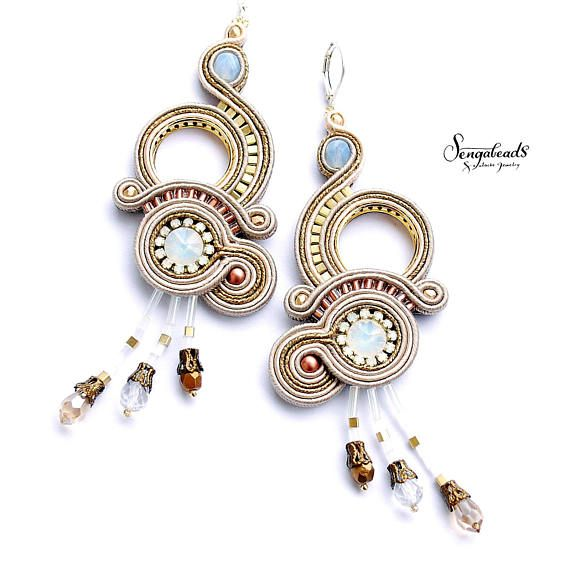 Long chandelier soutache earrings in gold, a little copper and white. Made with opal white crystals in the middle, Swarovski crystals, glass beads, Miyuki sead beads, soutache braid and sterling silver leverback earring clasps. Luxurious, sparkling design, embroidered with very much