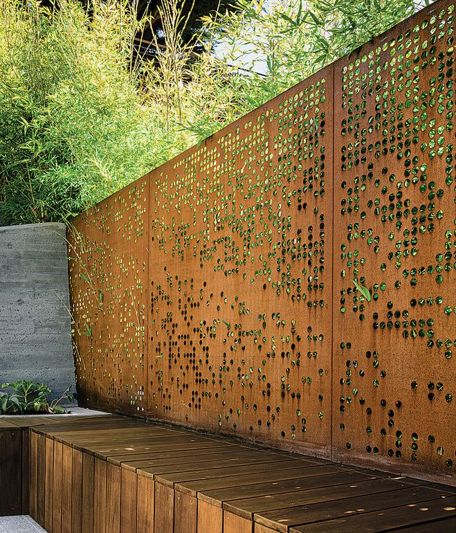 With input from her clients, Barensfeld used a computer to generate the circular patterns that were carved into a pair of Cor-Ten steel screens with a water-jet cutter. The perforations allow light and the green of the surrounding Koi bamboo to filter into the space while preserving privacy. Photo by Joe Fletcher .