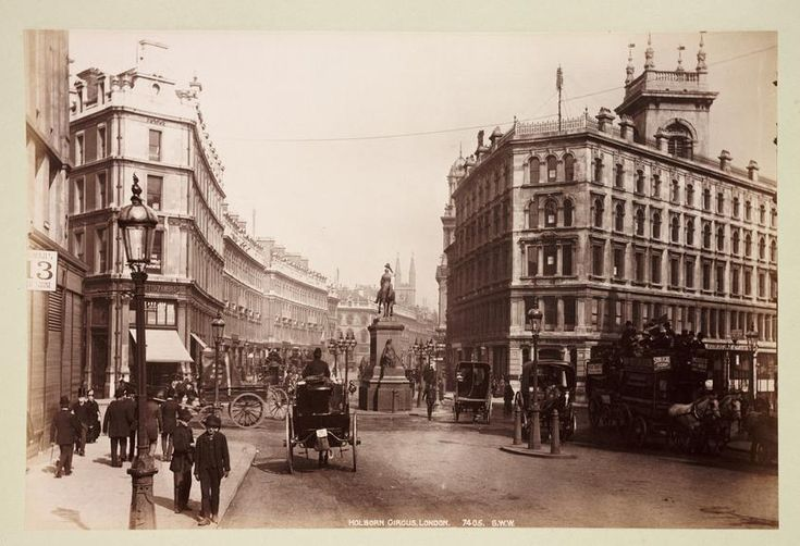 A photograph entitled 'Holborn Circus, London', published by George Washington Wilson, c. 1890. The back of the statue of Prince Albert (1819-1861) (1874) by Charles Bacon stands in the centre of the road. The premises of Negretti and Zambra, Instrument Makers, can be seen on the left.