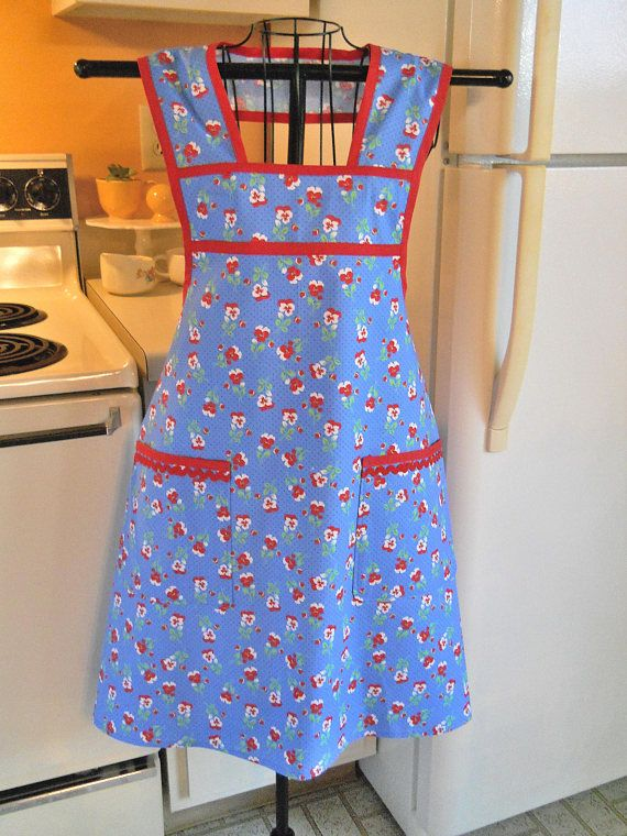 The 1930s reproduction fabric is perfect for this 1940s style apron The royal blue background really enhances the red and white flowers with green leaves. Its trimmed in red bias and rick rack. It is available for immediate shipping in sizes medium and large. Machine wash and dry