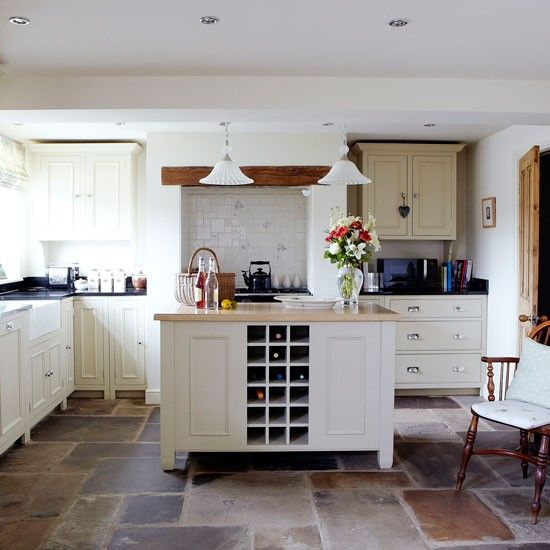 The kitchen has a rustic look with its pretty painted units and authentic flagstone floor reclaimed from a cowshed. A practical range cooker has been made pretty with subtle cream alcove tiles, while the island complete with integrated wine rack takes centre stage and offers additional storage and worktop space.   Similar tiles  Fired Earth Kitchen units Neptune  Read more at…