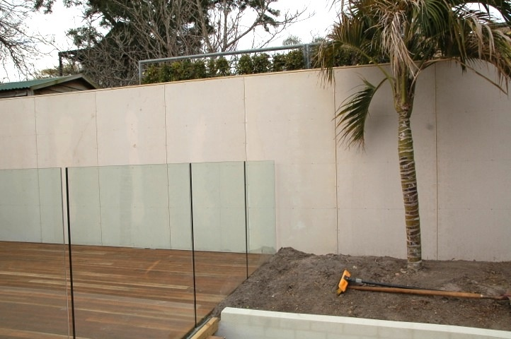 Decking added as well as a glass pool fence and rendered brick wall as part of the new garden area.
