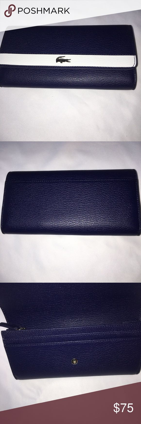 Lacoste navy and white wallet Cow leather. Snap closure. Outside open pocket. 4 large open pockets for dollar bills.  8 credit card pockets. Zip coin pocket in center of inside c Lacoste Bags Wallets
